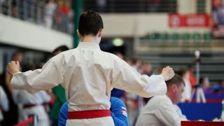 Karate kids competitions - trainer helps teenager fighter wearing kimono