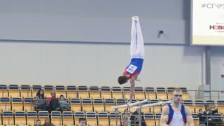 KAZAN, RUSSIA - APRIL 18, 2018: The championship of sports gymnastics - young athletic man performing on uneven bars
