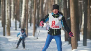 KAZAN, RUSSIA - MARCH, 2018: Young girl skier running on ski-track on cross-country skiing in sunny winter day