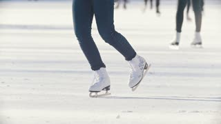 Legs of a teen girl skillfully skating on outdoor public ice rink, slow-motion