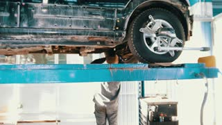 Lifted car in professional service - the collapse of convergence - process repairing, defocused background