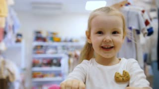 Little baby girl plays in toy's store for children