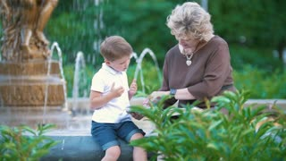 Little boy with grandmother sitting at the fountain in the park