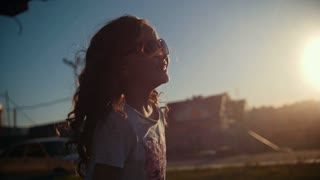Little caucasian girl playing and dancing outdoor at sunset, slow-motion