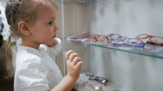 Little child -blonde girl in ophthalmology clinic chooses glasses