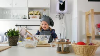 Little girl baker puts butter to the pastry dough for cooking biscuits