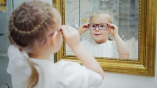 Little girl play with optics glasses - shopping in ophthalmology clinic