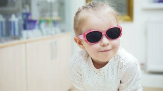 little girl playing and Hamming in front of a mirror and tries fashion medical glasses near mirror - shopping in ophthalmology clinic