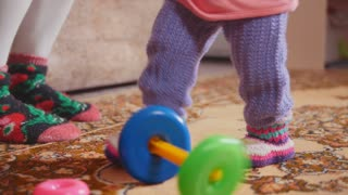 Little girl throwing and collecting the toys, focus on the legs and colored rings