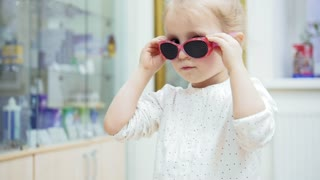 Little Girl tries medical fashion glasses and laughing at camera