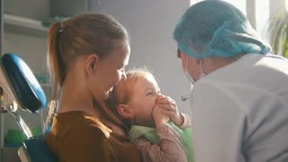 Little girl with mommy in dentist chair - child is playing