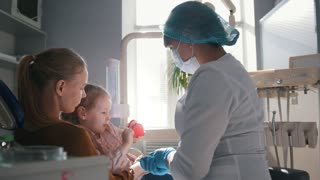 Little girl with mommy in dentist room - doctor examines the girl's teeth