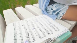 Little girl writes music notes sitting on the bench in the park