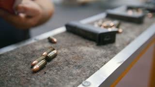 Loading bullets to pistol gun in shooting gallery