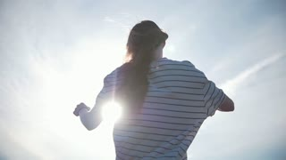 Long hair young woman flying in the wind at sunset