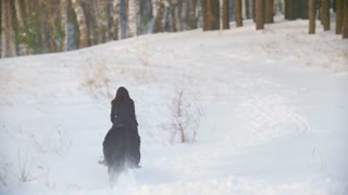 Longhaired female rider riding a black horse through the drifts in the winter snowy field