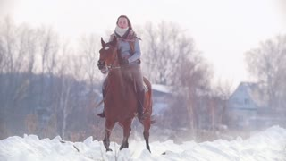 Longhaired female rider wild and fast riding black horse through the snow, slow-motion