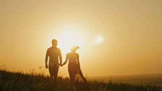 Love - brave young man and beautiful girl at sunset silhouette, slow-motion