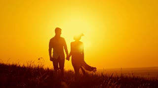 Loving couple - young man and beautiful girl walking at sunset meadow - silhouette