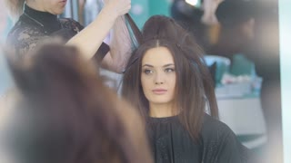 Make-up process at beauty shop for young black haired woman - visage and hair styling, close up