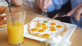 Male hands cuts a tasty and useful fried eggs with a knife and fork in restaurant