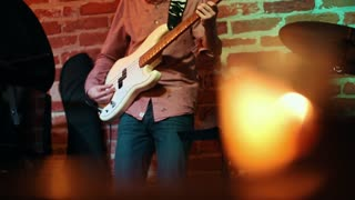 Male musician plays guitar at an evening in a jazz bar