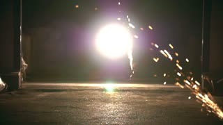 Male silhouette performs flips among the sparks from grinder at night