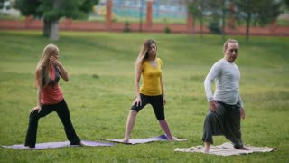 Man and women - sportsmen in park - performs yoga exercise outdoors in a green park