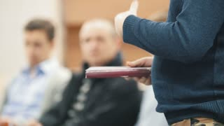 Man at business seminar speaking to audience and gesticulates