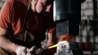 Man blacksmith in workshop forging red hot iron on anvil - small business