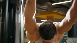 Man bodybuilder doing exercises for warm-up in the gym