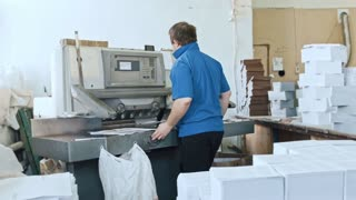 Man completes journal pages - manual labour - cutter guillotine machine at printing factory - typography