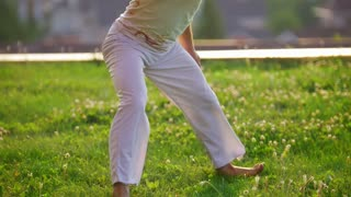 Man dancing capoeira on the grass, moves his legs in turn