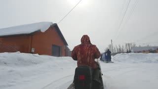 Man driving snowmobile in snowy village