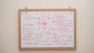 Man erasing formulas, graphs and charts from white board