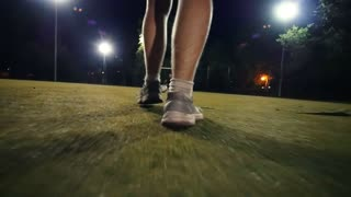 Man in sneakers walks to the ball and puts his foot on the ball, night shooting on the football field