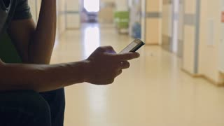 Man waiting in hospital and using smartphone, procrastination