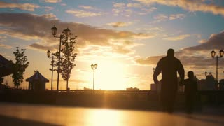 Man with a child walking at the quay past man carries young woman in a wheelchair at sunset