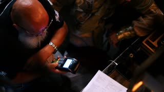 Man with big beard working in the bar accepting customer's cashless payment with credit card
