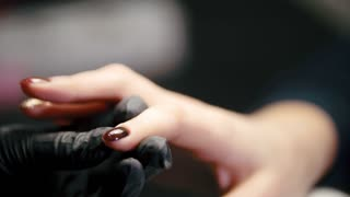 Manicure in beauty salon - cosmetic master in medical mask deals polish on the nails
