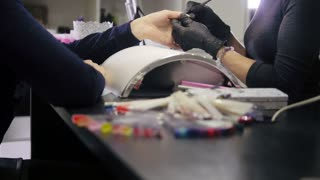 Manicure in beauty shop - cosmetic master in medical mask deals polish on the nails