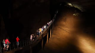 Many people tourists walking inside the big cave