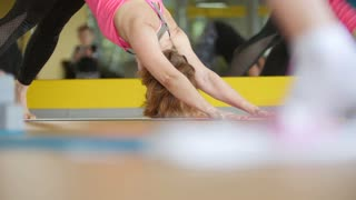 Mature women stretching out in fitness room - yoga training