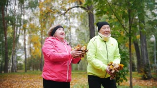 Mature women throwing leaves into the air in an autumn park. Smiling