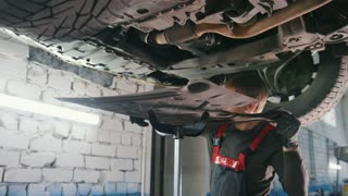 Mechanic at work - automobile's bottom under lifted car