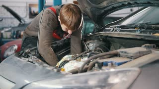 Mechanic checks and repairs automotive engine, car repair, working in the workshop, overhaul, under the hood