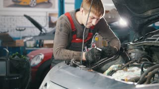 Mechanic checks and repairs automotive engine, car repair, working in the workshop, overhaul