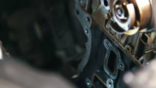 Mechanic cleans and wipes the car engine parts