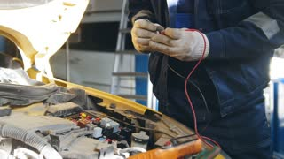 Mechanic in gloves checks electro fuse relay - electric components in car - automobile service diagnostics