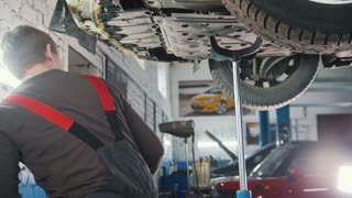 Mechanic unscrewing parts of automobile's bottom under lifted car